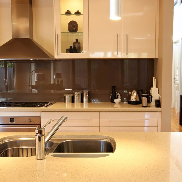 Modern kitchen, with granite benchtop, glass splashback, and view of hallway.